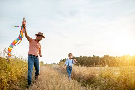 Father and son walking together with colorful air kite on the field during the sunset. Concept of a happy family Zdjęcie Seryjne