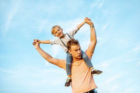 Portrait of a happy father with young son riding on the shoulders on the blue sky background outdoors. Concept of a happy family on a summer activity