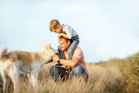 Ritratto di un padre felice con un giovane figlio che cavalca sulle spalle e il loro cane che si diverte sul campo. Concetto di una famiglia felice in un'attività estiva