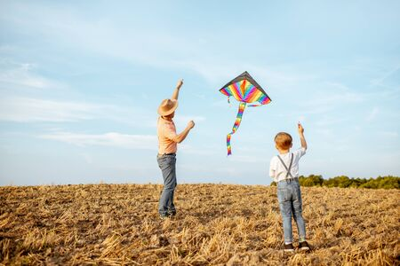 Father with son launching colorful air kite on the field. Concept of a happy family having fun during the summer activity Foto de archivo - 132048684