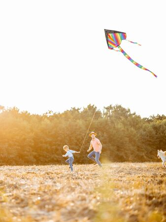 Father with son launching colorful air kite on the field on the sunset. Concept of a happy family having fun during the summer activity Foto de archivo - 132048916