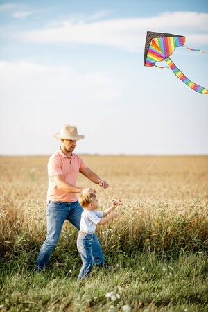 Father with son launching colorful air kite on the field during the sunset. Concept of a happy family having fun during the summer activity Zdjęcie Seryjne