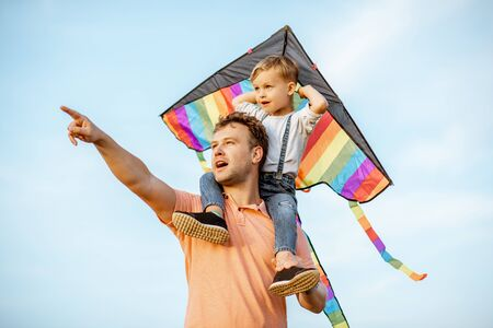 Portrait of a happy father and young son on the shoulders with colorful air kite on the blue sky background. Concept of a happy family and summer activity Zdjęcie Seryjne