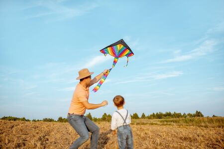 Father with son launching colorful air kite on the field. Concept of a happy family having fun during the summer activity Foto de archivo - 132049600