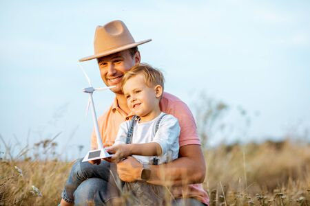 Father with young son playing with toy wind turbine in the field. Concept of knowledge of the green energy from the childhood