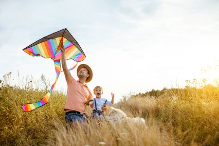 Portrait of a happy father and son holding colorful air kite while sitting together on the field during the sunset