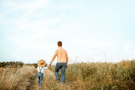 Father and young son walking keeping hands together on the field during the summer activity, back view