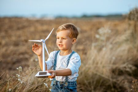 Curious young boy playing with toy wind turbine in the field, studying how green energy works from a young age 写真素材