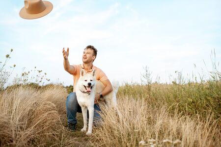 Happy man playing with dog on the field, throwing hat away