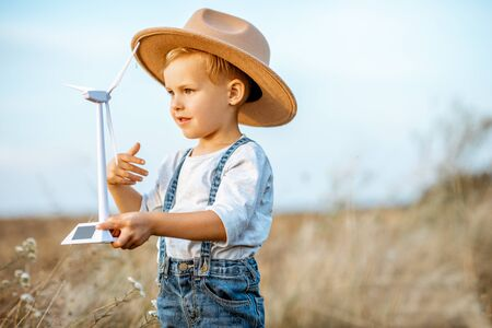 Portrait of a curious young boy playing with toy wind turbine in the field, studying how green energy works from a young age