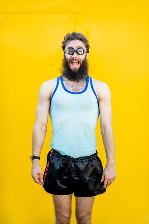 Portrait of a weird, old-fashioned swimmer dressed in 80s style with swimming glasses on the yellow background Stok Fotoğraf