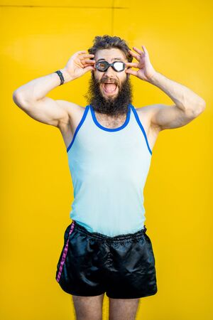Portrait of a weird, old-fashioned swimmer dressed in 80s style with swimming glasses on the yellow background Imagens