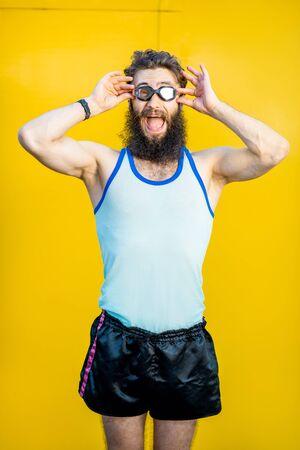 Ritratto di uno strano nuotatore vecchio stile vestito in stile anni '80 con occhiali da nuoto su sfondo giallo yellow