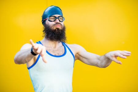 Portrait of a weird, old-fashioned swimmer dressed in 80s style with hat and swimming glasses on the yellow background