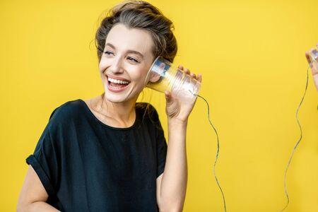 Heureuse femme écoutant une tasse, utilisant un téléphone à cordes sur fond jaune. Concept de communication et d'écoute