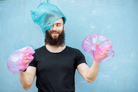 Portrait of confused man with plastic bags on hands and head standing on the green background. Concept of non-recyclable plastic pollution