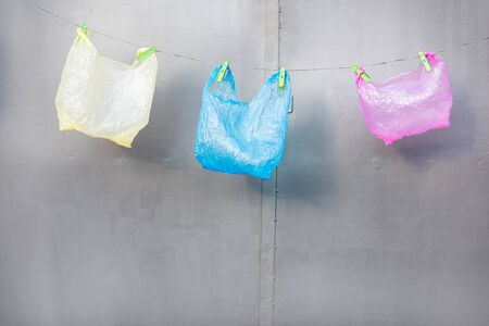 Three plastic bags hanging on the gray background. Concept of non-recyclable plastic pollution
