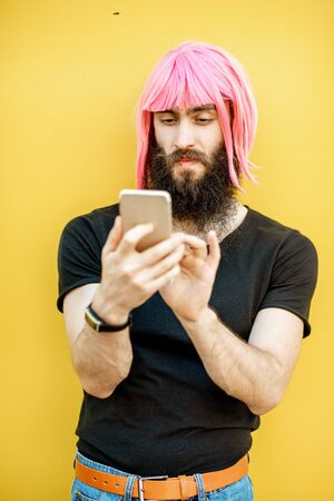 Funny portrait of a stylish man with beard and long color hair usning smart phone on the yellow background Stock Photo