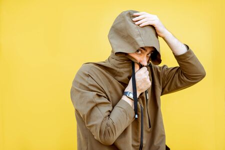 Portrait of a mysterious and weird man wearing hoodie coat on the yellow background Фото со стока