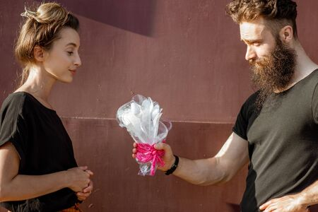 Man giving a bouquet made of plastic garbage to a young woman on the dark red background. Concept of non-recyclable plastic pollution