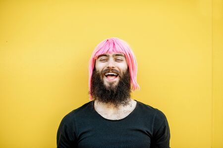 Funny portrait of a stylish playful man with beard and long color hair with expressive emotions on the yellow background