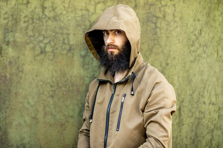 Portrait of a mysterious and weird man wearing hoodie coat on the green rusty wall background