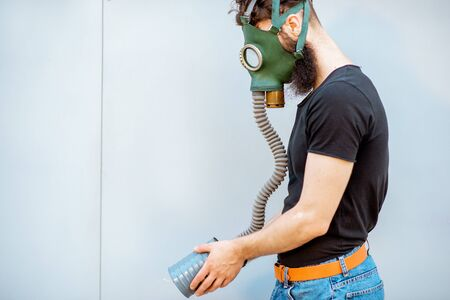Portrait of a man with gas mask on the grey background. Concept of poor ecology, air pollution and radiation hazards Banque d'images - 129241821