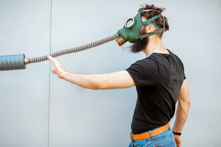 Portrait of a man with gas mask, pulling the pipe on the grey background. Concept of poor ecology, air pollution and radiation hazards Reklamní fotografie