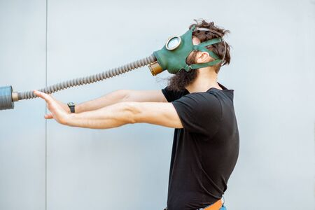 Portrait of a man with gas mask, pulling the pipe on the grey background. Concept of poor ecology, air pollution and radiation hazards Stock Photo