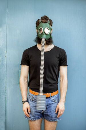 Portrait of a man with gas mask on the blue background. Concept of poor ecology, air pollution and radiation hazards