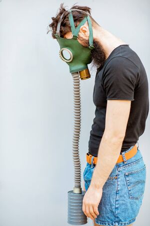 Portrait of a sad man with gas mask on the grey background. Concept of poor ecology, air pollution and radiation hazards Stock Photo