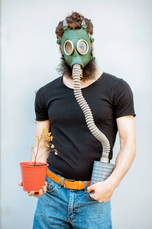 Portrait of a sad man with gas mask and dried flowerpot on the grey background. Concept of poor ecology, air pollution and radiation hazards Stock Photo