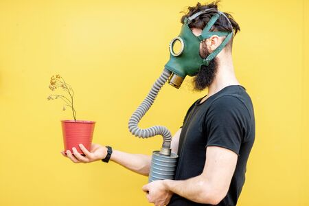 Portrait of a sad man with gas mask and dried flowerpot on the yellow background. Concept of poor ecology, air pollution and radiation hazards Stock Photo