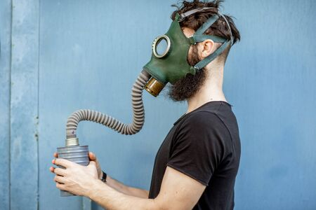 Portrait of a man with gas mask on the blue background. Concept of poor ecology, air pollution and radiation hazards Banque d'images - 129240518