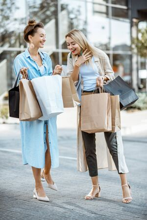 Two happy girlfriends feeling satisfied with purchases, standing together with shopping bags in front of the shopping mall outdoors