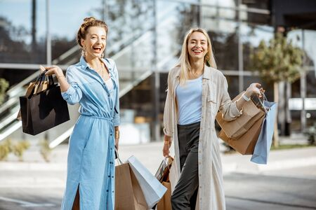 Portrait of two joyful and happy woman with shopping bags in front of the shopping mall, feeling excited with new purchases