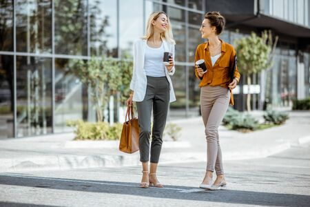 Full body portrait of a two young businesswomen walking with coffee cups near the modern office building outdoors