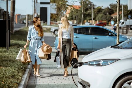 Women walking with shopping bags to their electric car on the shopping mall parking otudoors