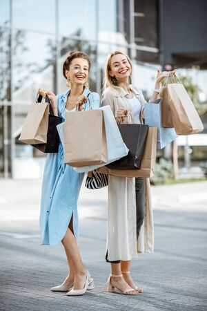 Two happy girlfriends feeling excited with purchases, standing together with shopping bags in front of the shopping mall 写真素材