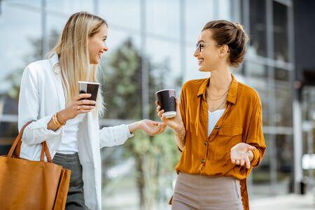 Dos jóvenes empresarias hablando cerca del edificio de oficinas, teniendo una pequeña charla durante la pausa para el café al aire libre.