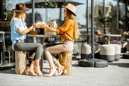 Two female best friends spending time together sitting with a gift on the terrace in a cafe, having fun during a summer day