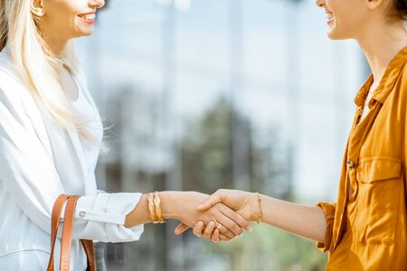 Two businesswomen having a deal shaking handsoutdoors, close-up view