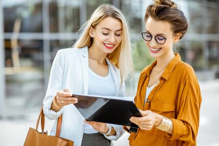 Portrait of a two young businesswomen standing with paper folder near the office building outdoors
