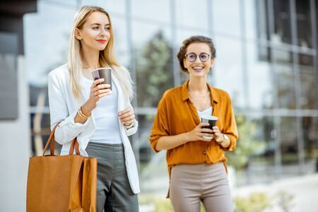 Portrait of a two young businesswomen walking with coffee near the office building outdoors 写真素材