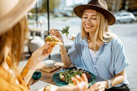 Zwei beste Freundinnen essen gesundes Essen, während sie an einem Sommertag zusammen auf einer Restaurantterrasse sitzen?