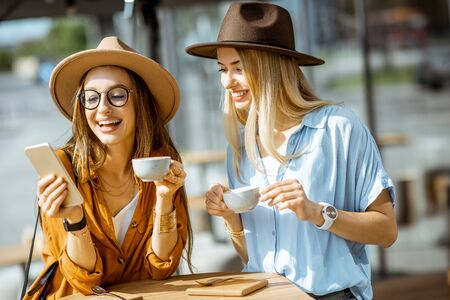Two female best friends spending time together on the cafe terrace, feeling happy standing with coffee and phone during a summer day