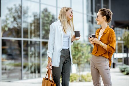 Two young businesswomen talking near the office building, having a small talk during the coffee break outdoors.