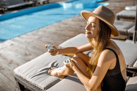 Młoda kobieta spryskuje twarz wodą, relaksując się na leżaku przy basenie Zdjęcie Seryjne