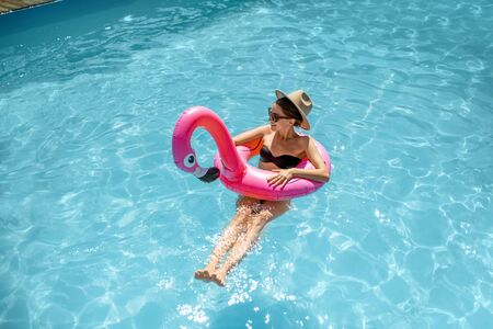 Woman in swimsuit and hat swimming with inflatable flamingo ring in the water pool, enjoying vacations during the summer time