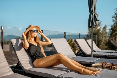 Young woman in swimsuit and hat lying on the sunbed at the resort with beautiful view on the mountains during the sunny day